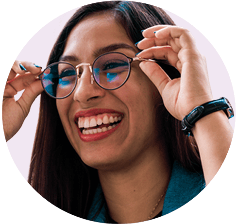 A smiling lady putting on her pair of glasses